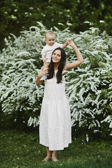 Young woman in a long white dress with a cute little baby boy in shirt and shorts walking at the green blossoming garden in summer day