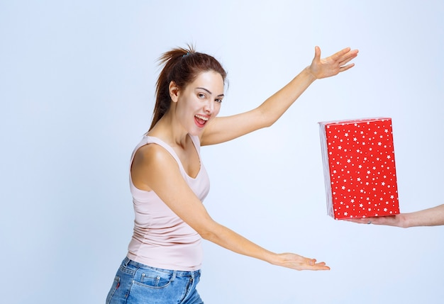 Giovane donna che non vede l'ora di prendere la scatola regalo rossa