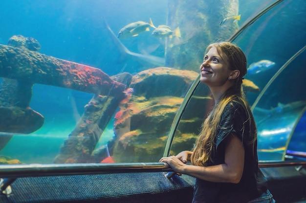 若い女性は海洋水族館のトンネルで泳いでいる魚を見てください