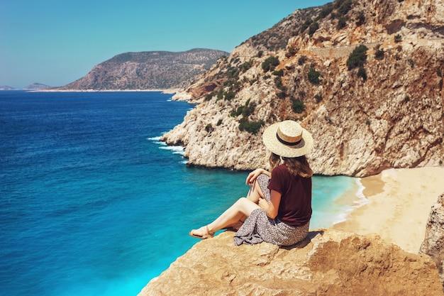 若い女性は美しいカプタスビーチを見渡して、休暇中の明るい夏の日にリュキア海岸を旅行します