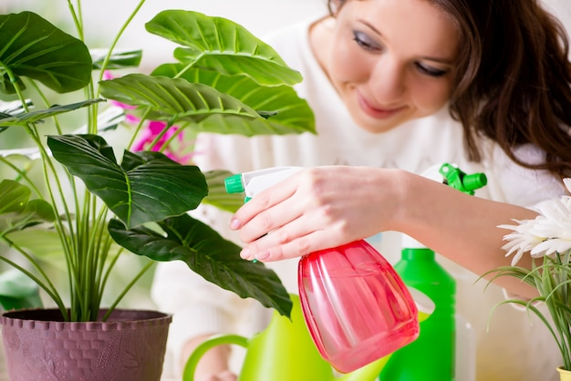 Young woman looking after plants at home