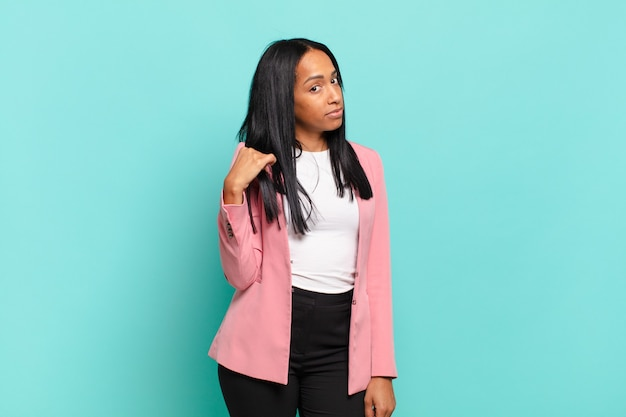 Young woman looking arrogant, successful, positive and proud, pointing to self