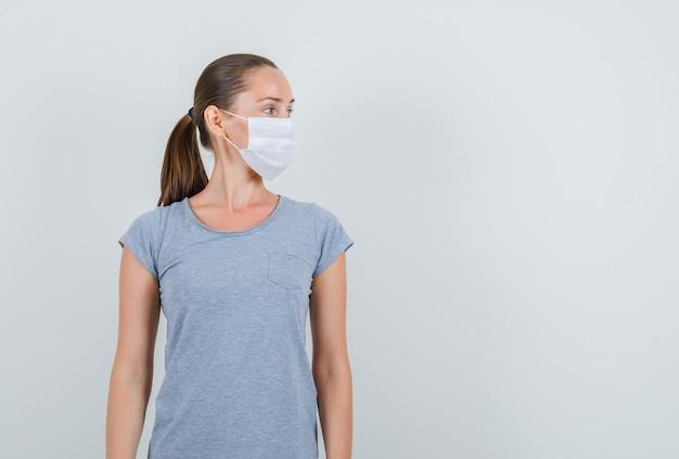 Giovane donna che osserva da parte in t-shirt grigia, maschera, vista frontale.