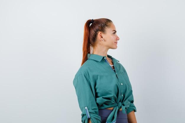 Молодая женщина смотрит в сторону в зеленой рубашке и смотрит вдумчиво, вид спереди.