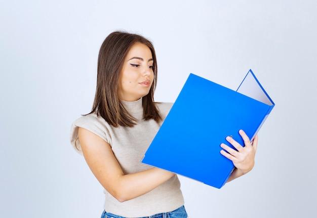 흰색 바탕에 파란색 폴더를보고 젊은 여자.