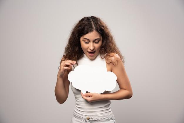 空の空白の白いスピーチのポスターを見ている若い女性。高品質の写真