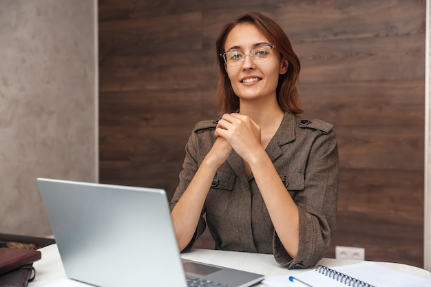 カメラを見て、ラップトップを使用して自宅で作業しながら笑顔の若い女性