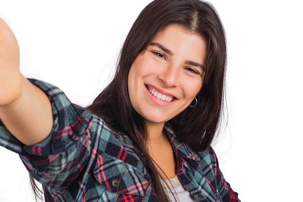 Молодая женщина смотрит в камеру и делает селфи.