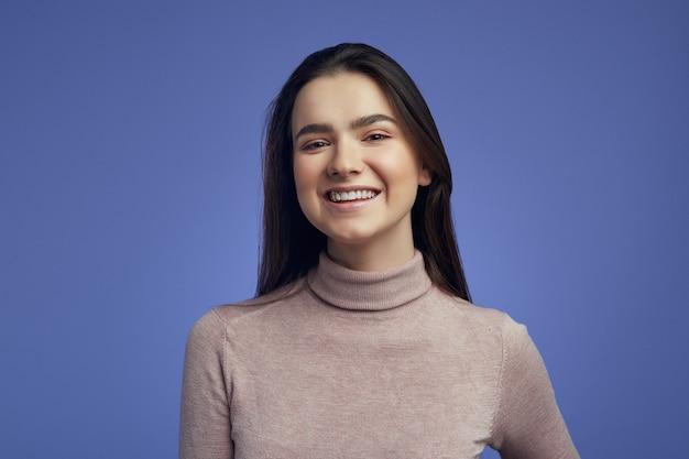 Молодая женщина смотрит в камеру с радостной и очаровательной улыбкой