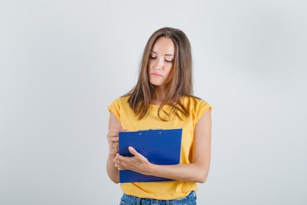 Молодая женщина смотрит в буфер обмена в футболке, шортах и выглядит занятой