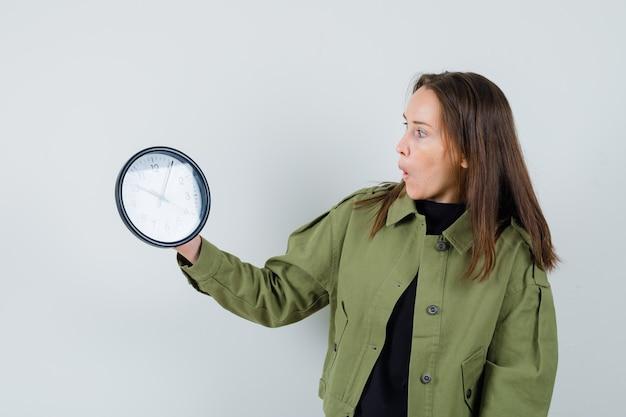 緑のジャケットの時計を見て、驚いて、正面図を見て若い女性。