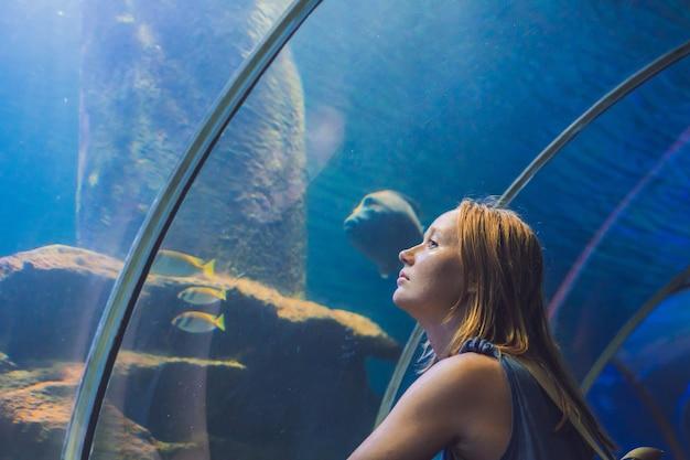 トンネル水族館で魚を見ている若い女性。