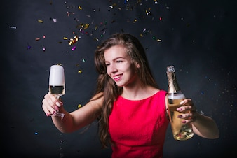 Young woman looking at glass of champagne