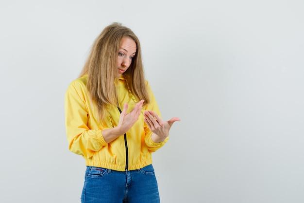 노란색 폭격기 재킷과 블루 진에 상상의 뭔가를 들고 놀 찾고 손을보고 젊은 여자. 전면보기.