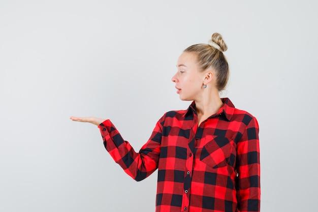 Молодая женщина смотрит на раздвинутую ладонь в клетчатой рубашке и выглядит сосредоточенной