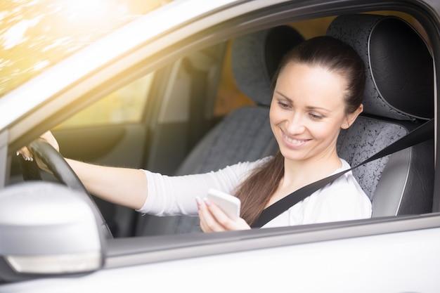 車で旅行している彼女の電話を見ている若い女性