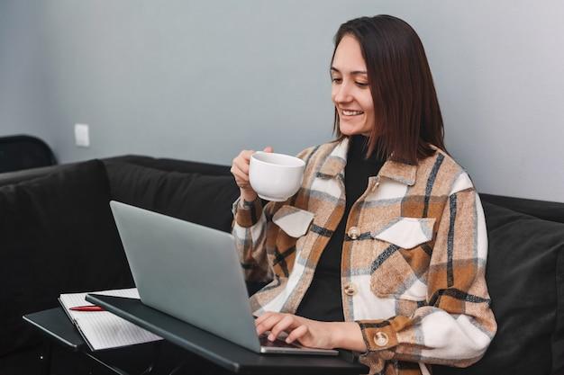 ソファに座って、お茶のマグカップを保持しながらノートパソコンを見ている若い女性