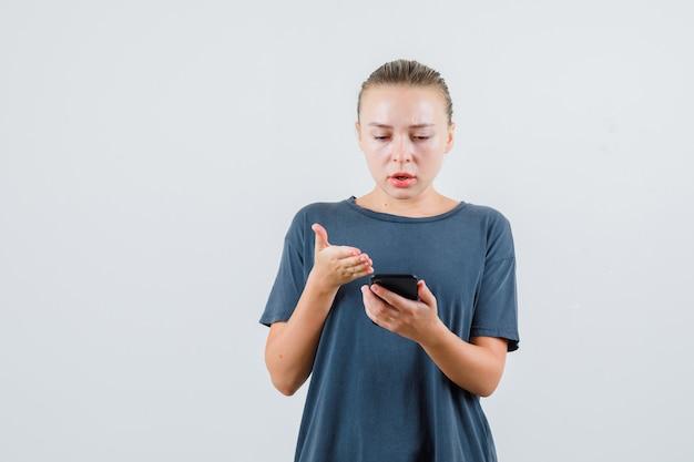 灰色のtシャツで携帯電話を見て混乱している若い女性