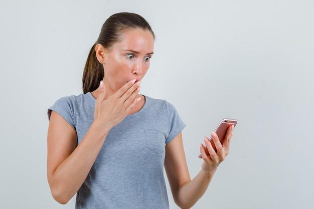 Молодая женщина смотрит на мобильный телефон в серой футболке и выглядит потрясенной. передний план.