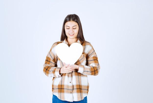 白い壁に紙のハート型のカードを見ている若い女性。