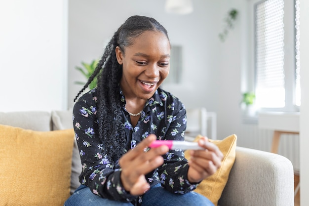 幸せで妊娠テストを見ている若い女性。ついに妊娠。妊娠検査を見て、自宅のソファに座って笑っている魅力的な黒人女性 Premium写真