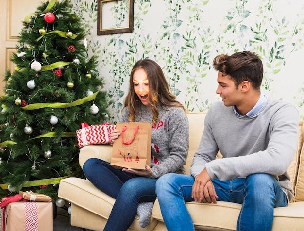 Молодая женщина, глядя на блестящий подарочный пакет