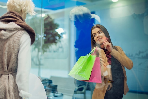 상점 창에서 보는 젊은 여자