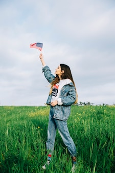 Young woman looking at small American flag in arm