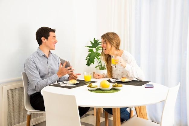 Молодая женщина, глядя на улыбающийся человек, показывая ее цифровой планшет на завтрак стол