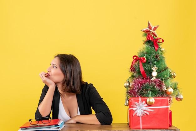 黄色のオフィスで飾られたクリスマスツリーの近くのテーブルに座っている何かを見ている若い女性