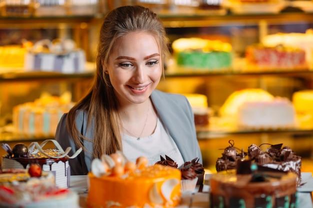 Молодая женщина смотрит в окно пекарни с кусочками тортов