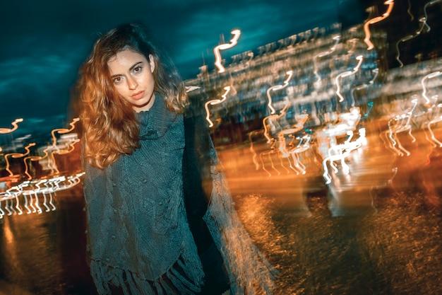 젊은 여자, 극적인 표정으로 카메라를 찾고. 밤에는 도시 배경에서.