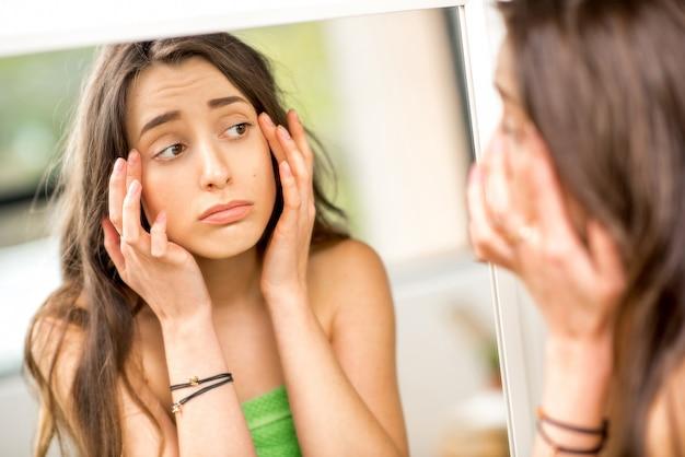 화장실에서 수건으로 서 있는 얼굴에 주름으로 고민하는 거울을 보고 있는 젊은 여성