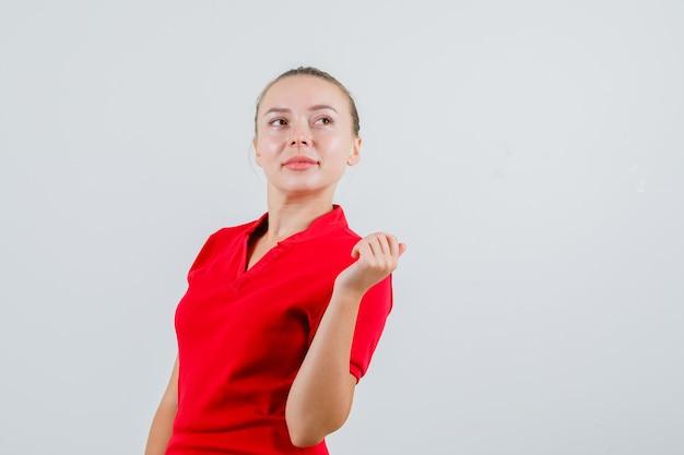 Giovane donna che guarda lontano in maglietta rossa e che sembra curiosa