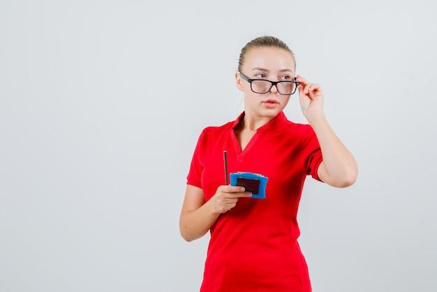 Молодая женщина смотрит в сторону, держа карандаш и буфер обмена в красной футболке, очках