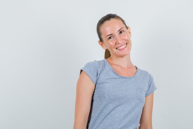 灰色のtシャツ、正面図で笑顔で目をそらしている若い女性。