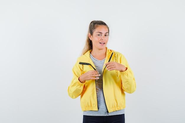 T- 셔츠, 재킷에 생각 하 고 유쾌 하 게 찾고있는 동안 멀리 찾고 젊은 여자. 전면보기.