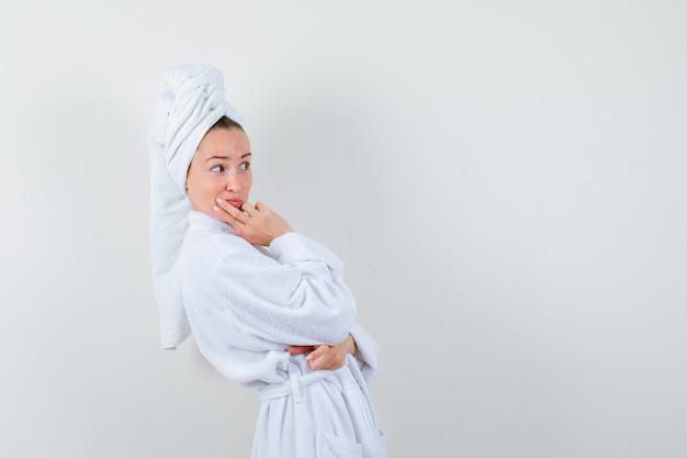 Молодая женщина смотрит в сторону с рукой на подбородке в белом халате, полотенце и смотрит с любопытством.