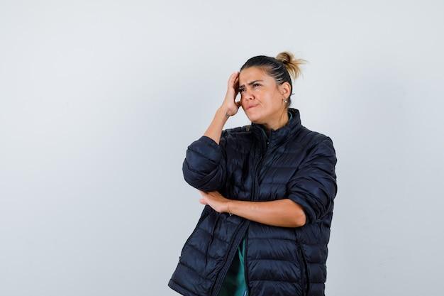 ダウンジャケットを着て頭を抱えて目をそらし、思慮深く見える若い女性。正面図。