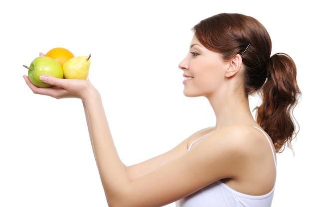 Giovane donna che guarda i frutti nelle sue mani