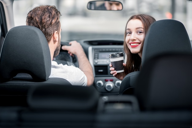 Young woman looking back sitting with coffee on the front seats and man driving a car
