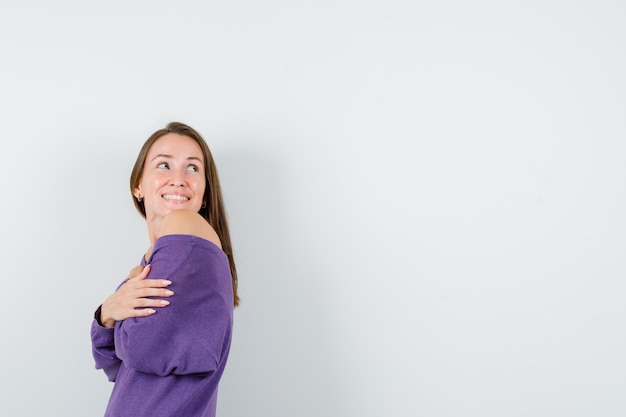 Young woman looking back while hugging herself in violet shirt and looking merry .