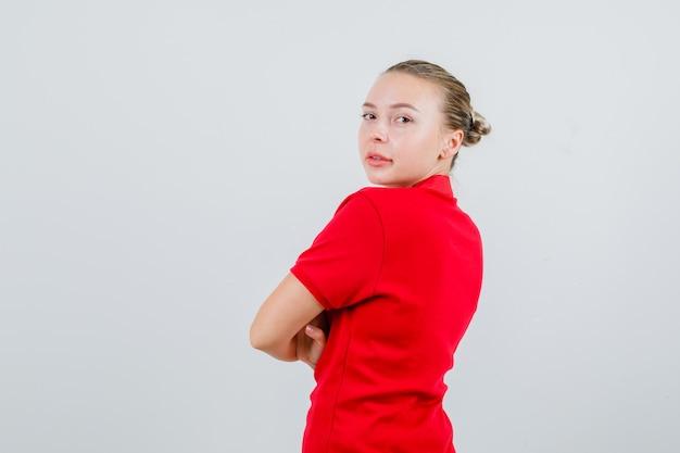 赤いtシャツを着て腕を組んで振り返り、自信を持って見える若い女性。 。