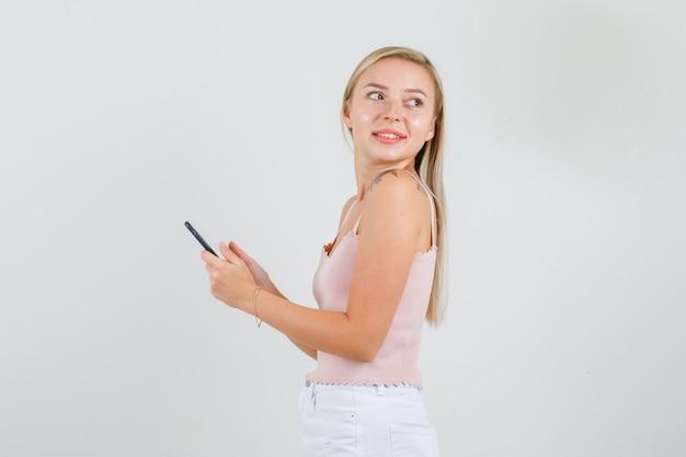 一重項でスマートフォンを手に振り返る若い女性