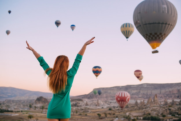 Young woman looking balloons arms outstretched
