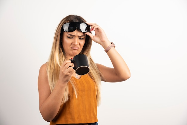 Young woman looking on black cup and wearing goggles.