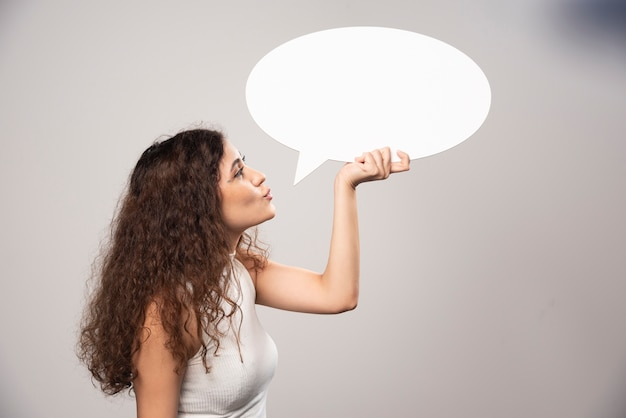 Young woman looking at blank white speech bubble. high quality photo