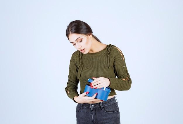 Giovane donna che guarda il contenitore di regalo blu con l'espressione sorpresa.