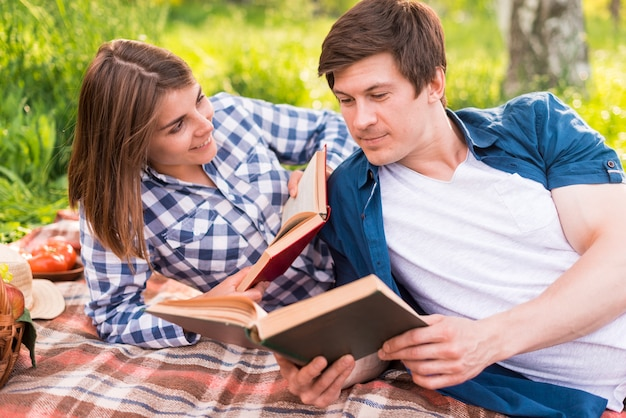 Young woman looking at boyfriend reading book