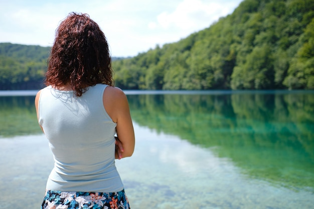 A young woman looking to a calm lake in plitvice national park, croatia